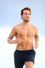 Fitness sports runner man jogging on beach