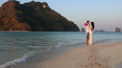 bride and groom hug standing in water against island