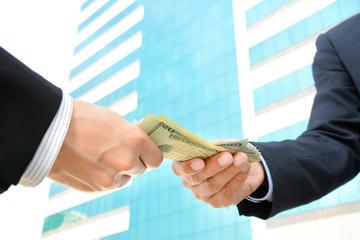 Hands of businessmen passing money, US dollar bills