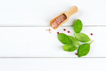 fresh basil leaves, salt and pepper on wooden surface