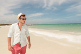 Handsome young man walking on the beach,