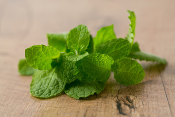 fresh mint leaves on wooden surface
