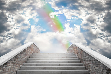 Marble staircase leading to the cloudy sky and rainbow