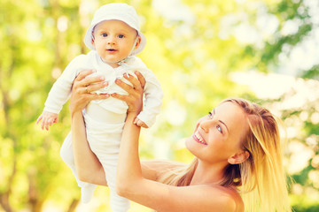 happy mother with little baby in park
