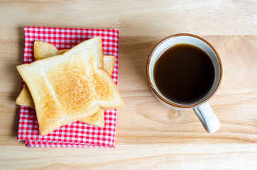 Coffee and toasts on wooden table