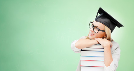 happy student in mortar board cap with books