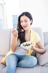 Pretty brunette looking at camera and eating salad on couch