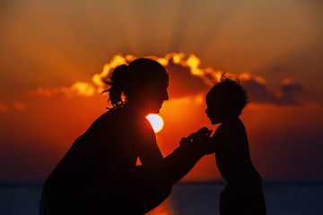Happy mother and joyful son sunset silhouette