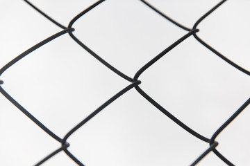 close up of mesh fence over gray sky