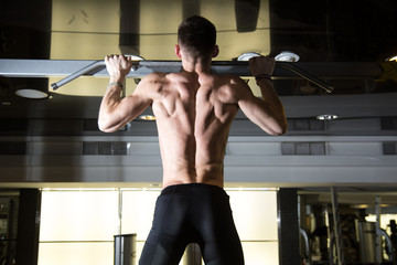 Fitness man doing pull-ups in a gym for a back workout