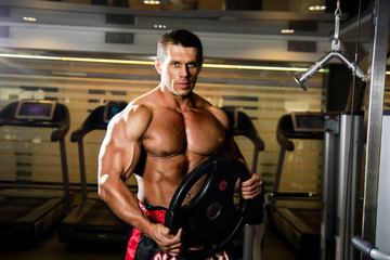 Handsome muscular man in the gym. Weightlifter with the disc.