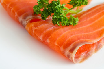 Salmon slices with parsley on white.