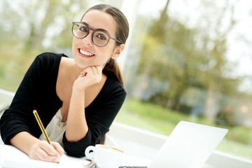Thoughtful young businesswoman sitting working