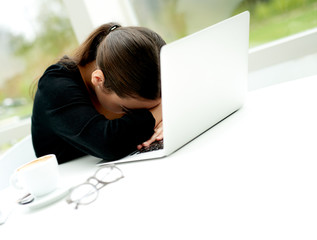 Despondent businesswoman leaning over her laptop