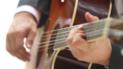 european man plays guitar with focus moving along neck