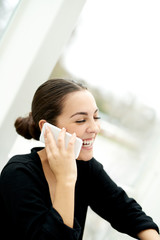 Joyful young woman chatting on her mobile