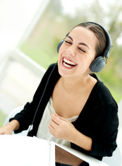 Joyful young woman laughing and listening to music