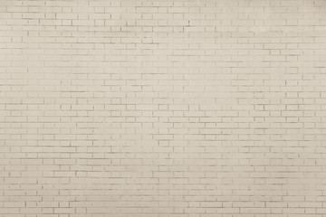 the pale beige textured surface of a brick wall