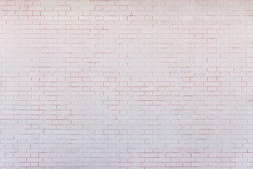 the pale pink textured surface of a brick wall