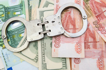 Crime and Money. Handcuffs are on the dollar, euro and ruble
