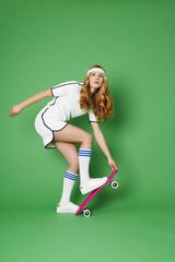 Beautiful skateboarder in studio