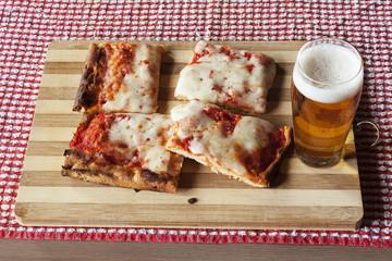 Tranci di pizza margherita e birra su tagliere di legno