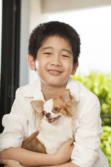 kid life, an Asian boy hug his Chi hua hua tiny dog