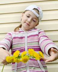 the young girl does a wreath of yellow flowers of a dandelion