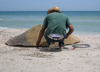 man working on the beach with parasol