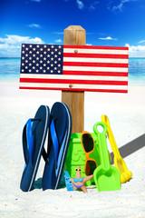 Holzschild mit USA Flagge am Strand