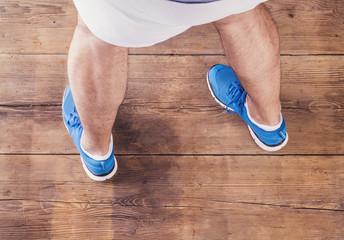 Legs of a runner. Studio shot on wooden background.