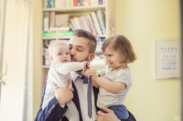 Young businessman with his daughters in his arms