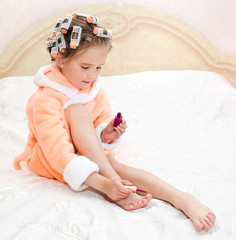 Cute funny little girl polishing her nails