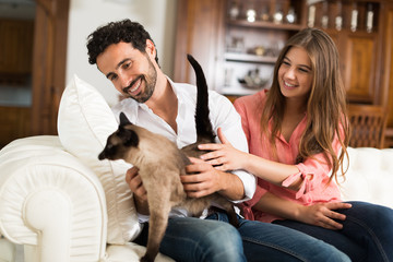 Happy couple playing with their cat on the couch