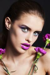 Портрет девушки вблизи с макияжем на чёрном фоне