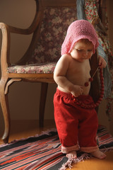 Little girl blonde in a pink knit beret near the old armchair