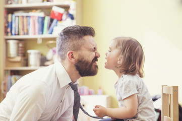 Young father spending time with his little daughter at home