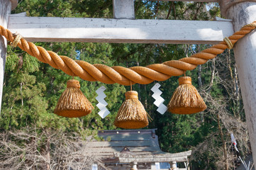 Shimenawa hang at the gate in front of the Japanese shrine