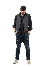 Modern trendy man with hands in pockets looking down