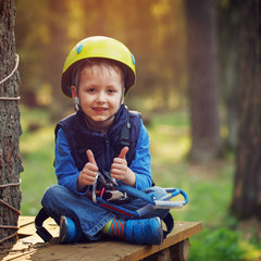 brave little boy having fun at adventure park and giving double