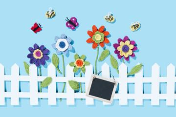 gehäkelte Blumen und Insekten mit Schild, blauer Hintergrund