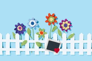 gehäkelte Blumen am Zaun mit Schild und Herz, blauer Hintergrund