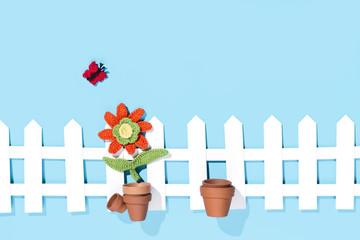 gehäkelte Blume im Topf am Gartenzaun und einem Schmetterling