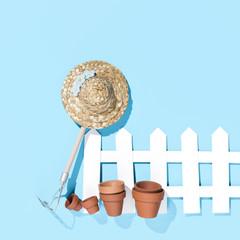 Zaun mit Harke, Hut und Töpfen, blauer Hintergrund
