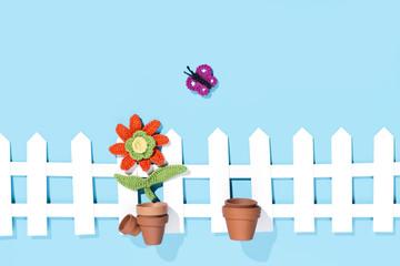 Blume im Topf am Zaun mir Schmetterling, blauer Hintergrund