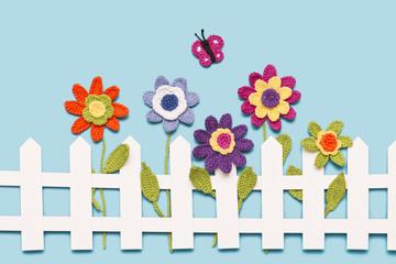 gehäkelte Blumen am Gartenzaun mit Schmetterling