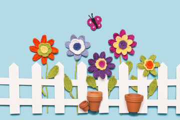 gehäkelte Blumen mit Zaun, Blumentöpfen und einem Schmetterling