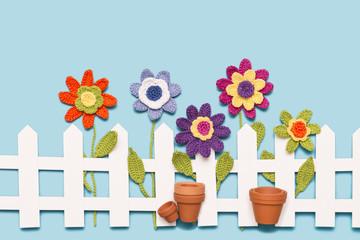 gehäkelte Blumen mit Zaun und Blumentöpfen