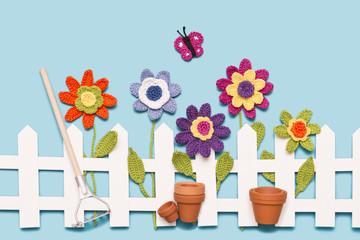 Blumen am Zaun mit Harke, Töpfen und einem Schmetterling
