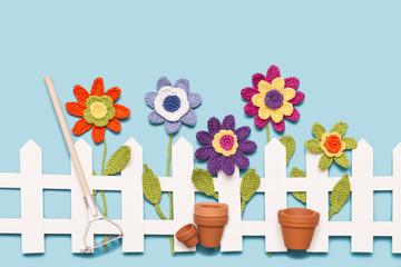 gehäkelte Blumen am Zaun mit Harke und Blumentöpfen